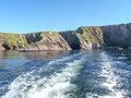 Stern wash from a fishing boat with the slea head on the dingle peninsula in ireland with a clear deep blue sky Royalty Free Stock Image