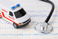 Stethoscope and ambulance car on ecg Royalty Free Stock Photos