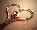 Stethoscope heart shape in of on a graph of the patient s heartbeat Royalty Free Stock Images