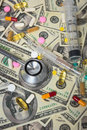 Stethoscope with hypodermic syringe and doze of medical tablets on u s dollar banknotes Stock Image