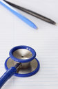 A stethoscope on lined study paper with pens Stock Image