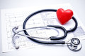 Stethoscope lying on ecg diagram with a red heart the top of the chart Stock Photos