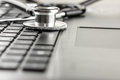 Stethoscope lying on a laptop keyboard low angle close up view of the disc of depicting online healthcare and medical advice Stock Photography