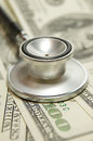 Stethoscope on money background and pills Royalty Free Stock Photo