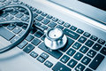 Stethoscope over a computer keyboard toned in blue Royalty Free Stock Photo