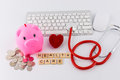 Stethoscope with piles of coins, red heart, piggy bank, saving f Royalty Free Stock Photo
