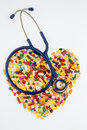 Stethoscope and pills in heart shape tablets shaped arrangement symbol photo of disease diagnosis medication Royalty Free Stock Photo