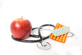 Stethoscope with pills and red apple close up isolated on white background healthy food diet concept choice fitness or illness Stock Image
