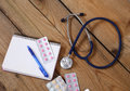 Stethoscope and tablets isolated on wooden background Royalty Free Stock Photo
