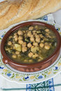 Stew of chickpeas and spinach with cod on a table with a tablecloth Royalty Free Stock Images