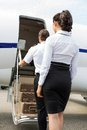 Stewardess and pilot boarding private jet rear view of Royalty Free Stock Photography
