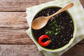 Stewed black beans with spices and herbs in a bowl close-up. hor Royalty Free Stock Photo