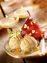 Stewed pear served with ice cream on a plate and two candles in the background Royalty Free Stock Photos