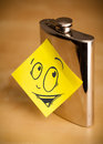 Sticky note with smiley face sticked on hip flask