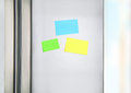 Sticky notes on the fridge three colorful paper door refrigerator for message little reminder sheets communication Stock Photo