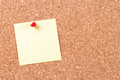 Sticky post pinned on cork board blank empty yellow it bulletin with red pin ready for your message Stock Images