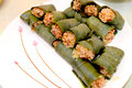 Sticky rice steamed in bamboo wrapped and leaves on a white plate Royalty Free Stock Images