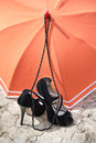 Stiletto heels, necklace and umbrella on a cracked earth Royalty Free Stock Photo