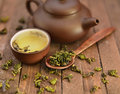 Still life with asian tea set and raw tea leaves clay pot small round cup full of fresh green spoon dry on wooden background in Stock Images