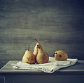 Still life with autumn pears on linen a gray table Stock Photos