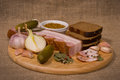 Still life bacon appetizer on round wooden board dijon mustard bread garlic onion pickles and sackcloth background Stock Photos