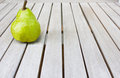 Still life with a big green pear on a white wooden table. Royalty Free Stock Photo