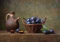Still life with black plums in a basket Royalty Free Stock Photo