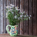 Still life with blue asters in vase on wooden background Stock Photography