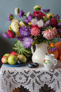 Still life with the bouquet of asters plums pumpkins and a water melon located on a table on a white cloth laces against a Royalty Free Stock Photo
