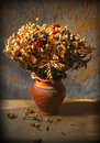 Still life with bouquet of dried roses in clay vase grunge background Stock Photos