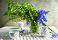 Still life bouquet polygonatum blue tones white crockery with a of and Stock Photo
