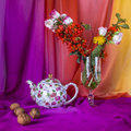 Still life with bouquet summer flowers, teapot and walnuts