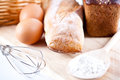 Still life of bread flour eggs and kitchen utensil on a wooden board Royalty Free Stock Image