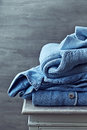 Still life with casual cotton sweaters on a chest of drawers Royalty Free Stock Images