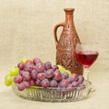 Still life with ceramic bottle, grape and glass Stock Images