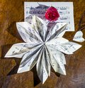 Still life composition made with a musical score folded in the shape of a flower and a red rose
