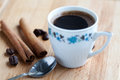 Still life with cup of coffee. Vintage bowl, spoon and beans cinnamon sticks on wooden background. soft focus, macro Royalty Free Stock Photo