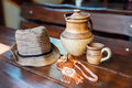 Still life of cups, a pitcher of red clay, hats and decoration of national ornament on the wooden table Royalty Free Stock Photo