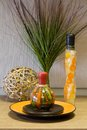 Still-life decorative bottles, straw sphere, leaf and the ceramic plate Stock Photography
