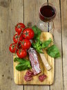 Still life of delicacy salami tomatoes and basil rustic style Stock Images