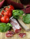 Still life of delicacy salami tomatoes and basil rustic style Royalty Free Stock Photos