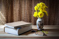Still life flower and book books on the wooden table near vase of yellow glasses Stock Photo