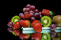 Still life of fresh fruit on a black background and berries closeup Royalty Free Stock Photos