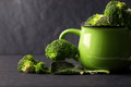 Still life with fresh green broccoli in ceramic cup on black sto Royalty Free Stock Photo