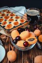 Still life with a glass bowl with apricots and cherries, cottage cheese pie, coffee on a wooden table Royalty Free Stock Photo
