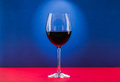 Still life glass of wine with nice light effect in red and blue background Royalty Free Stock Photo