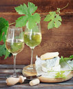 Still life with glasses of white wine bottle and cheese Stock Image