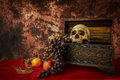 Still life with a human skull with fake apples and grapes