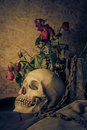 Still life with a human skull with a red rose in vase beside the timber and chains Royalty Free Stock Photos