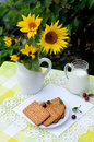 Still life with jug of milk cookies and a bouquet of decorative sunflowers Royalty Free Stock Image